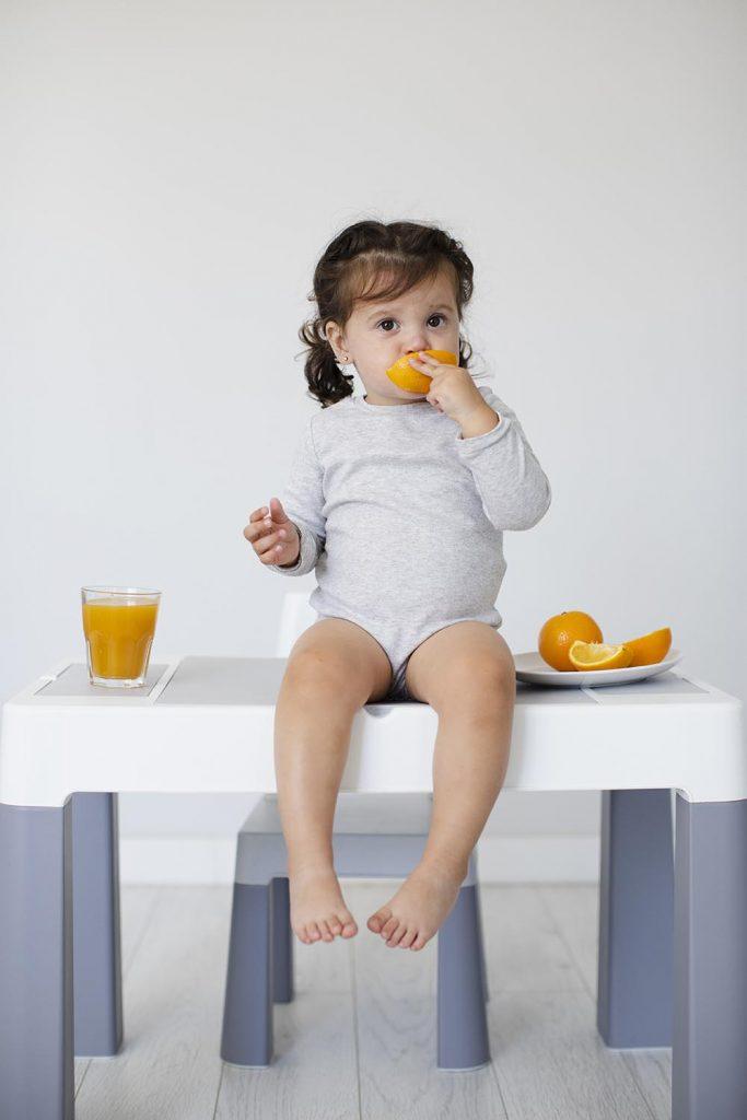 crianca chupando laranja
